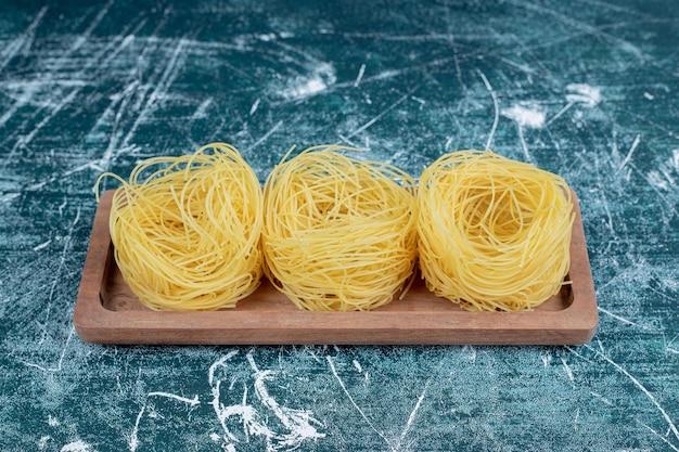 Pile de nids de spaghettis crus sur planche de bois.