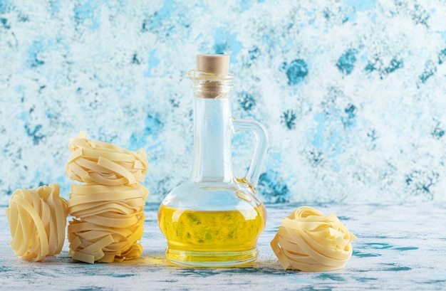 Pile de nids de tagliatelles et verre d'huile d'olive sur fond bleu.