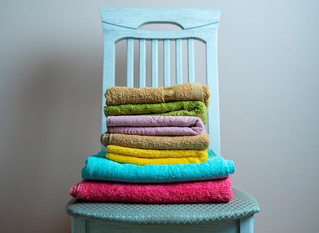 Une pile de nouveaux textiles de serviettes de couleur fraîche et propre sur l'étagère de la lessive