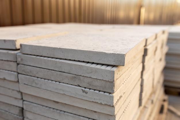 Pile de nouvelles dalles de pavage en pile. matériaux de construction sur un chantier de construction
