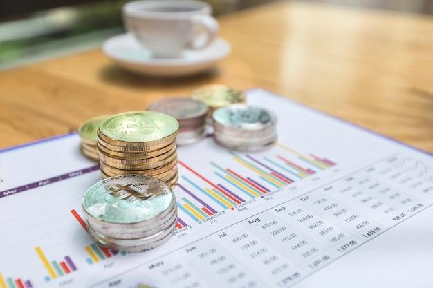 Pile d'or et d'argent bitcoins (cryptocurrency) sur papier graphique