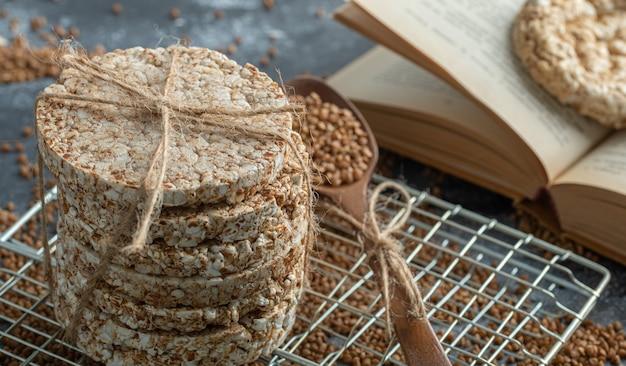 Pile de pain croustillant, sarrasin et livre sur une surface en marbre