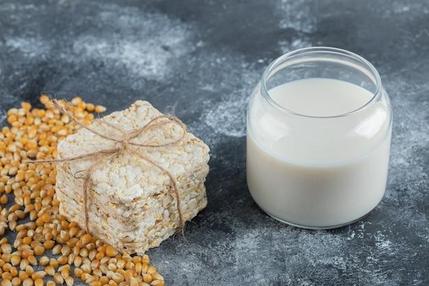 Pile de pain croustillant et verre de lait sur marbre.