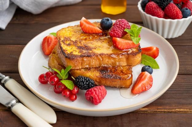 Une pile de pain perdu sur une assiette avec des baies fraîches, des pétales d'amandes et du miel