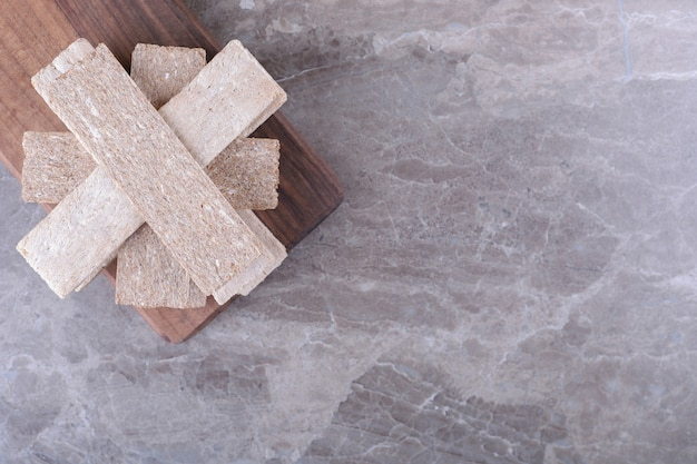 Une pile de pains croustillants sur la planche de bois, sur la surface en marbre
