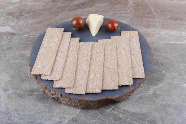 Une pile de pains croustillants, tomates, fromage sur la planche de bois, sur la surface en marbre