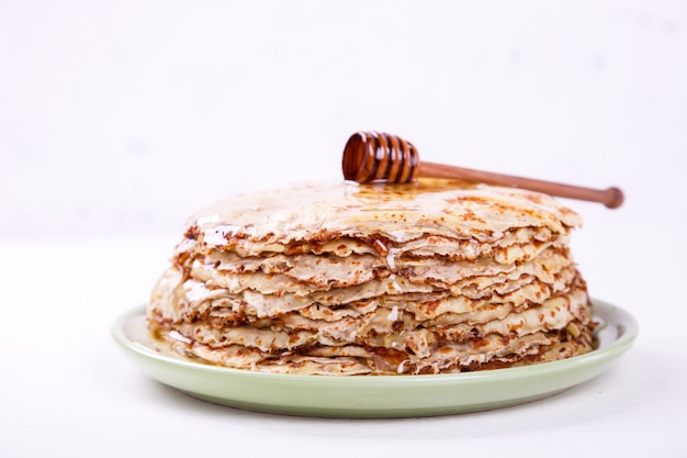 Pile de pancakes minces avec radition au miel