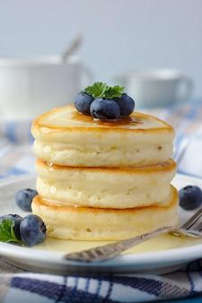 Une pile de pancakes scotch avec du miel et des bleuets sur une table de petit déjeuner