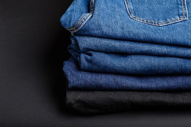 Pile de pantalons en jean bleu. pile de jeans bleus sur fond noir avec espace de copie.