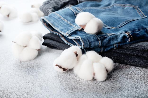 Pile de pantalons jeans et fleurs de coton sur table lumineuse
