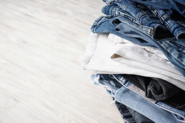 Pile de pantalons jeans sur fond de bois clair, place pour le texte.