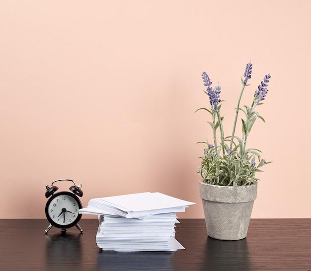 Pile de papiers blancs, un pot en céramique de lavande et un réveil