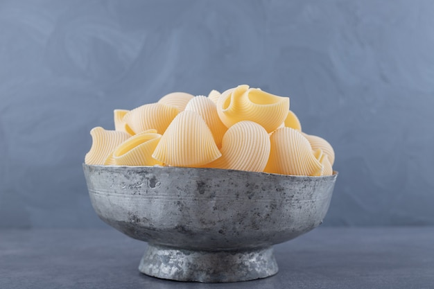 Pile de pâtes conchiglie dans une tasse classique.
