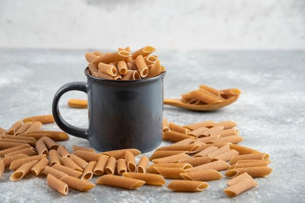 Pile de pâtes diététiques brunes avec une tasse noire sur une surface grise.