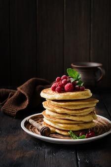 Pile de petites crêpes maison au miel, framboises fraîches et groseilles rouges sur une vieille surface en bois.