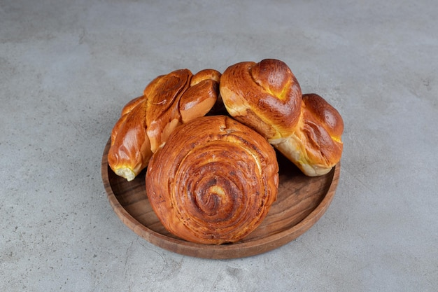 Pile de petits pains sucrés, sur un petit plateau sur une table en marbre.