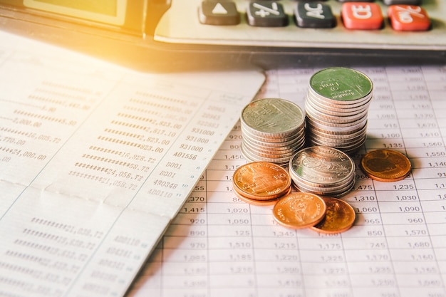 Pile de pièce d'argent sur papier de feuille de comptabilité avec calculatrice