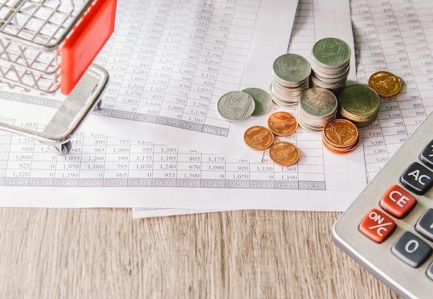 Pile de pièces d'argent sur papier comptable avec calculatrice et petit panier