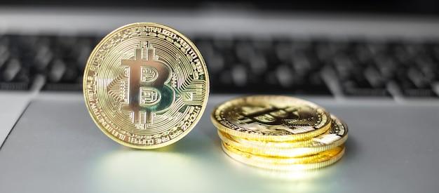 Pile de pièces de crypto-monnaie bitcoin d'or sur clavier d'ordinateur portable