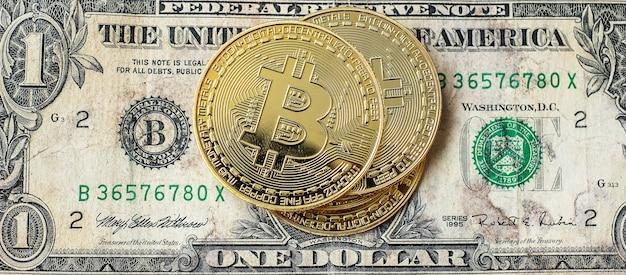 Pile de pièces de crypto-monnaie bitcoin d'or sur fond de dollar américain.
