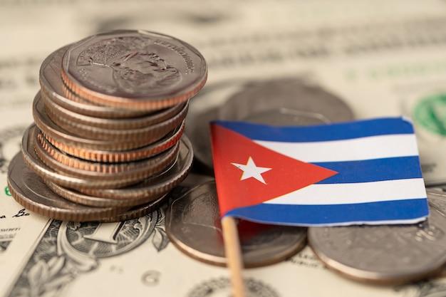 Pile de pièces avec drapeau de cuba sur fond de billets en dollars américains.