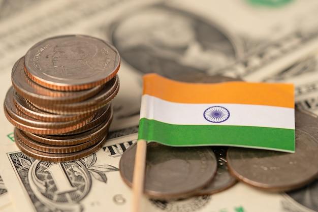 Pile de pièces avec le drapeau de l'inde sur les billets en dollars.