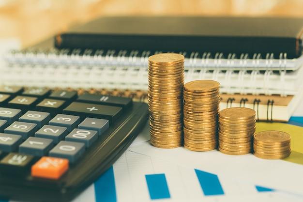 Pile de pièces et feuille de papier graphique financier avec calculatrice sur la table de travail, vision de planification d'entreprise et concept d'analyse financière.