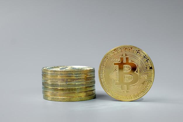 Pile de pièces de monnaie bitcoin d'or sur fond gris