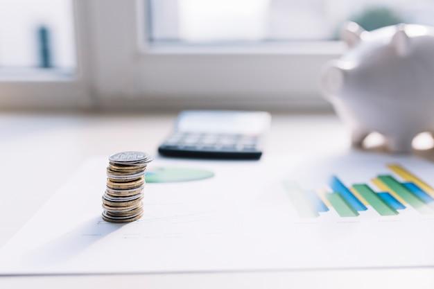 Pile de pièces de monnaie sur le graphique avec la calculatrice et la tirelire au-dessus de la table