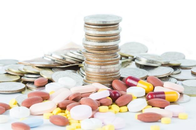 Pile de pièces de monnaie avec idée de concept de capsule médicale.