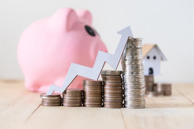 Pile de pièces de monnaie et tirelire, concept d'épargne et d'investissement avec un graphique croissant sur le dessus