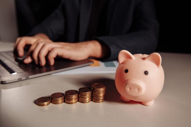 Pile de pièces de monnaie et tirelire rose au bureau