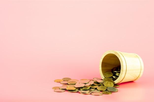 Pile de pièces d'or du panier en bois sur fond rose.