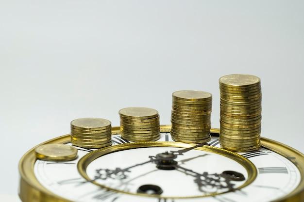 Pile de pièces d'or sur horloge vintage