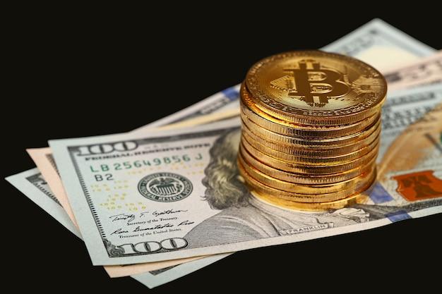 Pile de pièces physiques bitcoin d'or sur les billets en papier en dollars américains