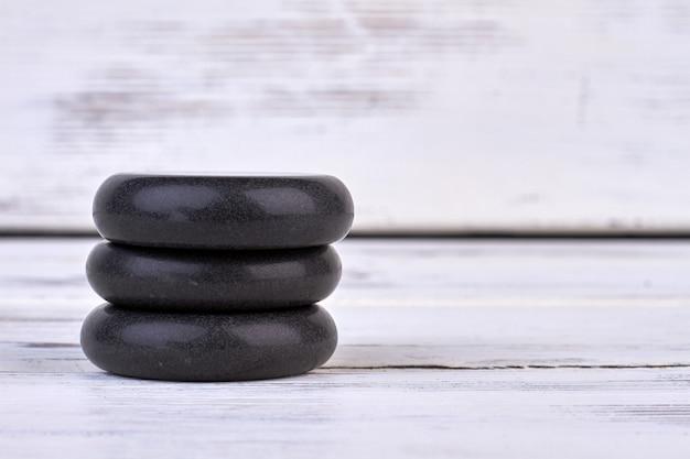 Pile de pierres chaudes spa sur fond de bois blanc. trois pierres noires pour spa.