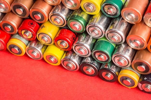 Pile de piles usagées sur fond rouge