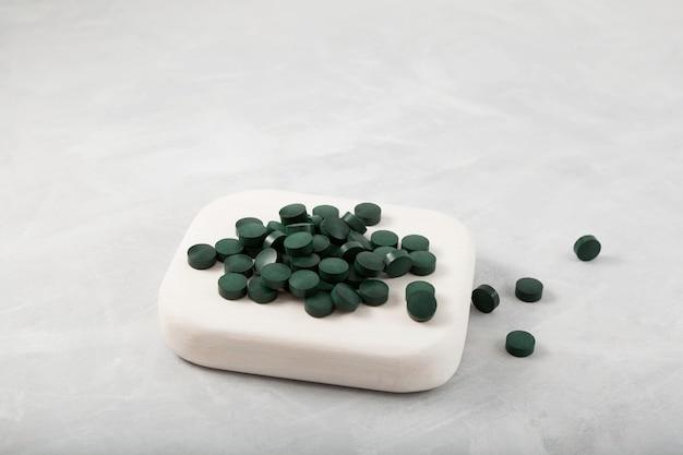 Pile de pilules vertes sur podium en bois blanc chlorelle et spiruline naturelles sous forme de comprimés