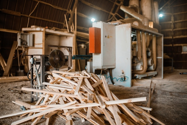 Pile de planches près de la machine à bois dans la sciure de bois, personne, industrie du bois, menuiserie. traitement du bois en usine, sciage forestier dans la cour à bois, scierie