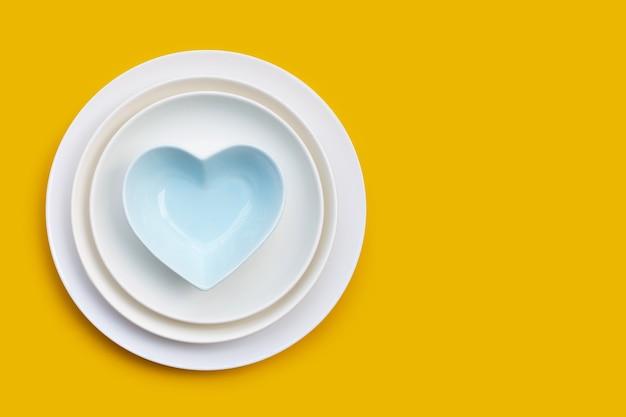 Pile de plats sur fond jaune. copier l'espace