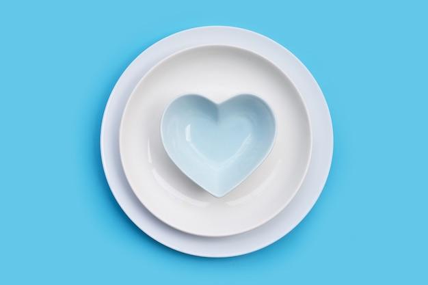 Pile de plats sur table bleue. copier l'espace