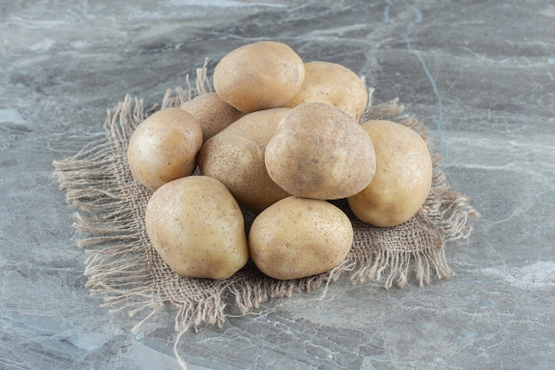 Une pile de pommes de terre sur le dessous de plat sur la table en marbre.