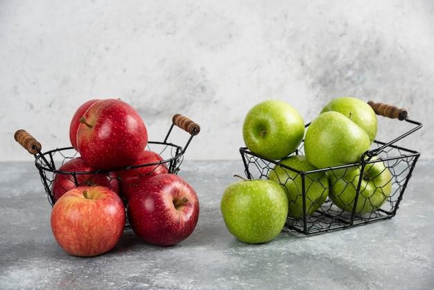 Pile de pommes vertes et rouges fraîches placées dans des paniers métalliques.