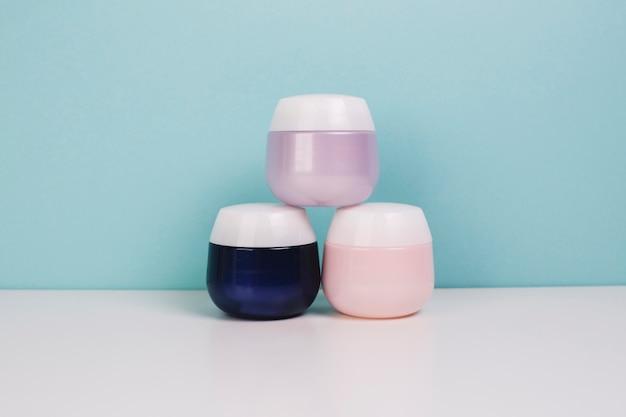 Pile de pots de cosmétiques