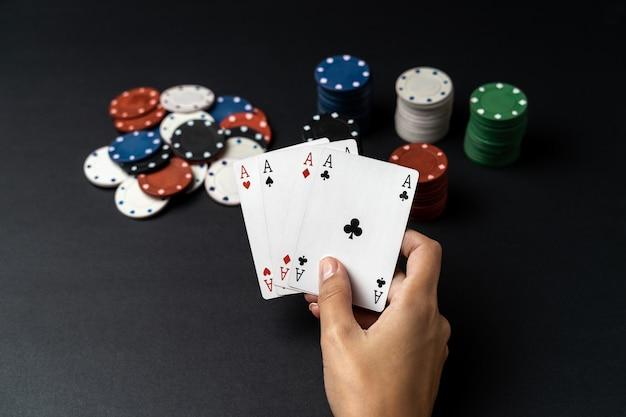 Pile de puces et main de femme avec quatre as sur la table. concept de jeu de poker