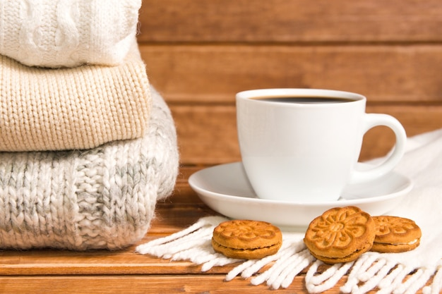 Pile de pull chaud tricoté confortable, fond en bois.