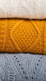 Une pile de pulls automne-hiver en tricot confortable aux couleurs jaune, blanc et bleu. nettoyage et organisation de l'espace, vêtements. garde-robe.