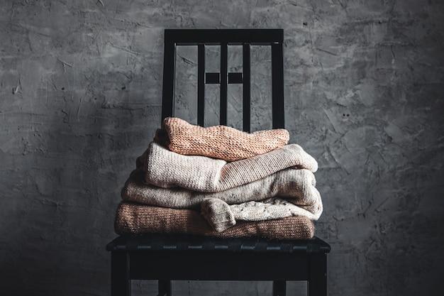 Une pile de pulls confortables chauds tricotés, sur une chaise par le mur gris