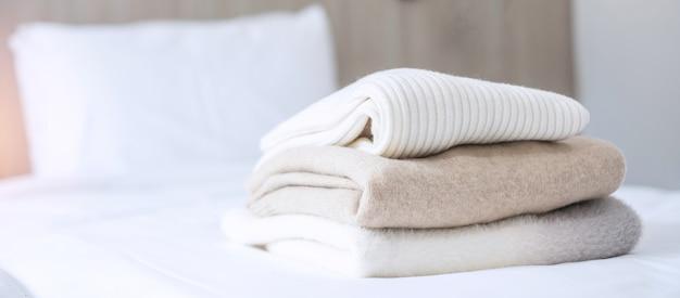 Pile de pulls en laine beige sur le lit dans un hôtel de luxe ou un complexe ou à la maison. détente, vêtements d'automne ou d'hiver, concepts de blanchisserie et de vacances