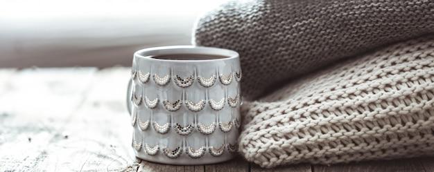 Une pile de pulls et une tasse de thé